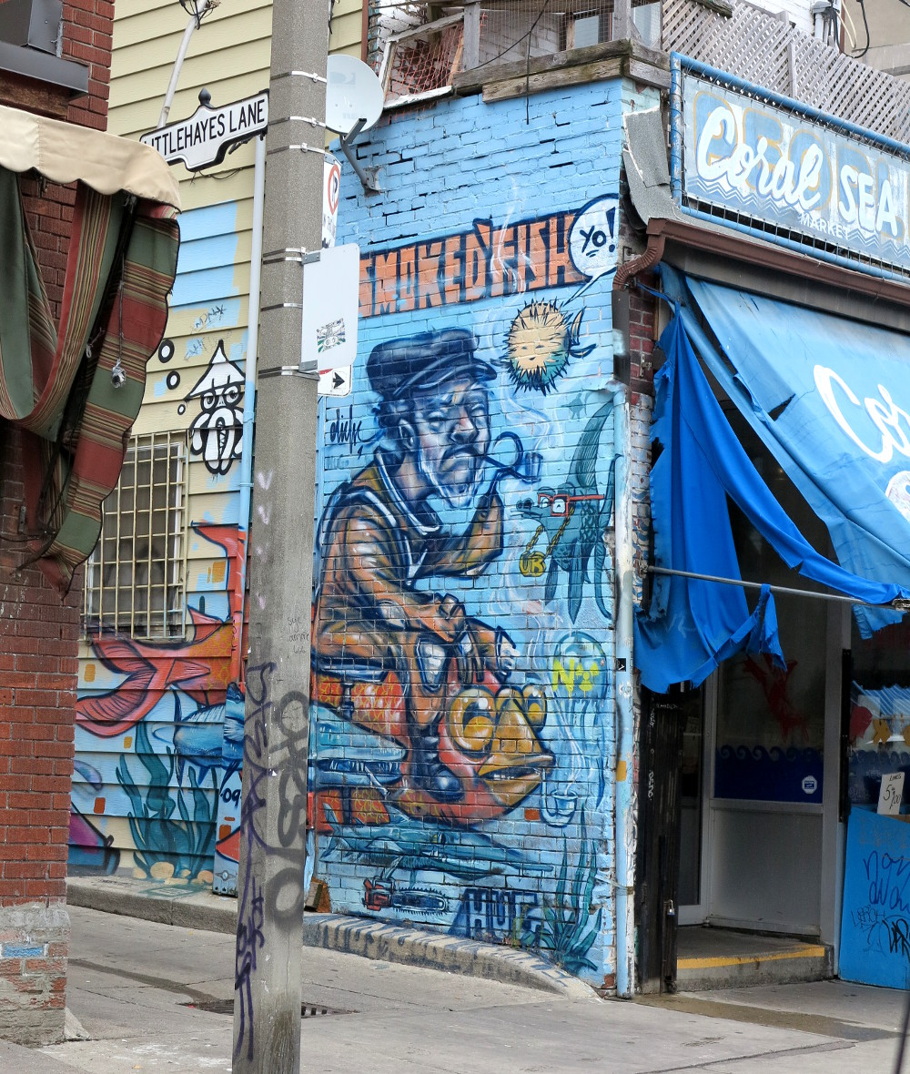 Man with a fish graffiti in Kensington Market Double-Barrelled Travel