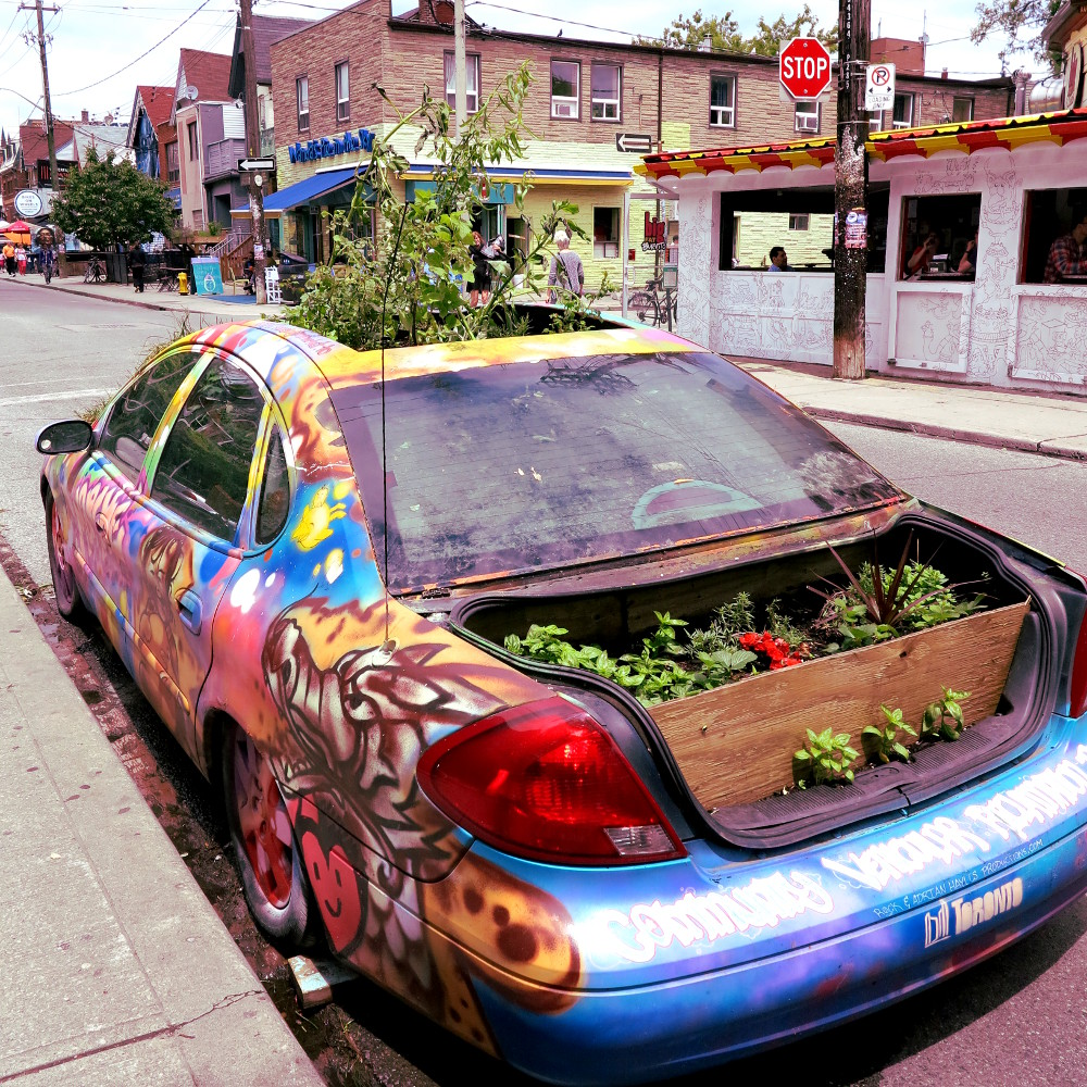 Plant covered car at Kensington Market Double-Barrelled Travel