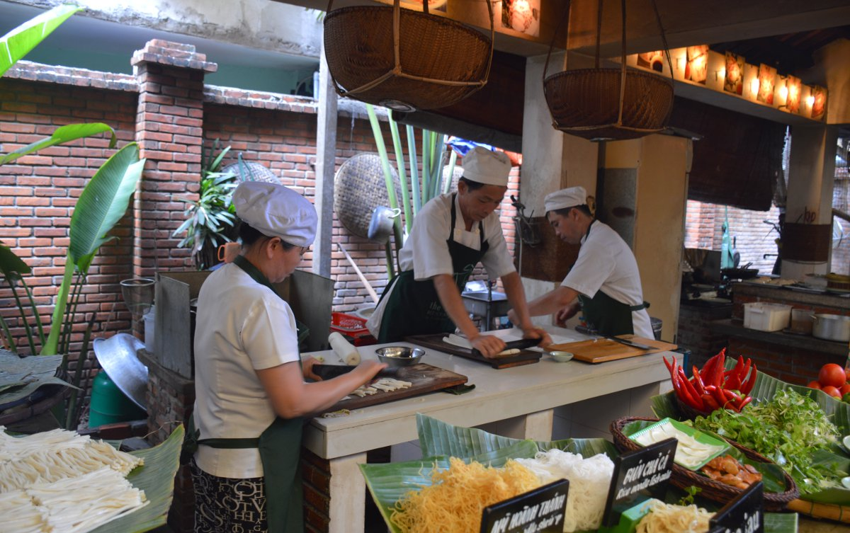 Ms Vy's chefs hard at work rolling and cutting freshly made rice noodles by hand
